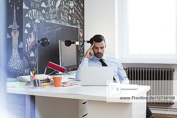 Businessman in creative office using laptop at desk