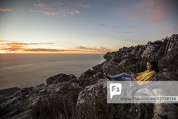 South Africa  Cape Town  Table Mountain  woman sitting on a rock drinking wine at sunset