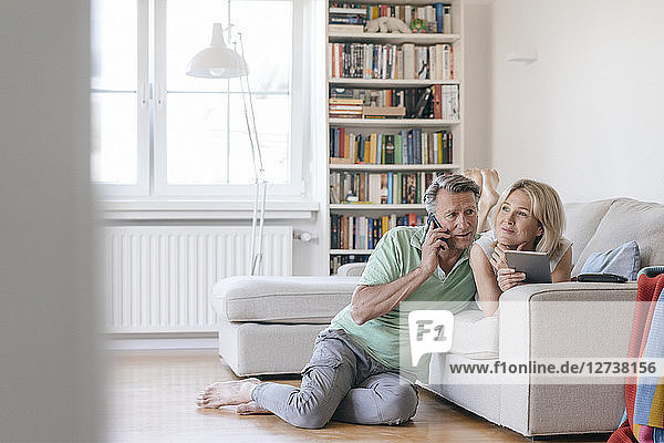 Mature couple at home using cell phone and tablet