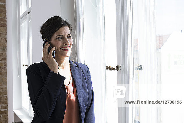 Smiling businesswoman on the phone at the window