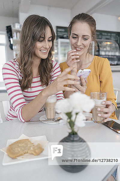Two girlfriends meeting in a coffee shop  using smartphone
