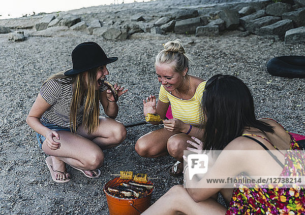 Three young women sitting together having a barbecue