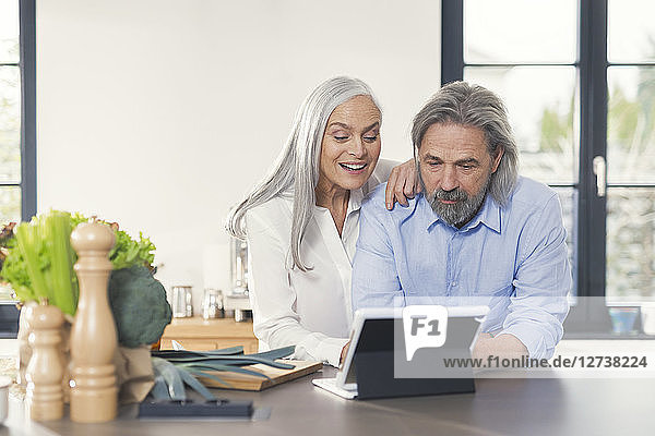 Happy senior couple preparing food in kitchen with online recipe