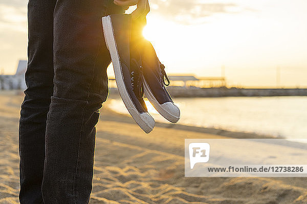 Spain. Man holding shoes  at a beach during sunrise