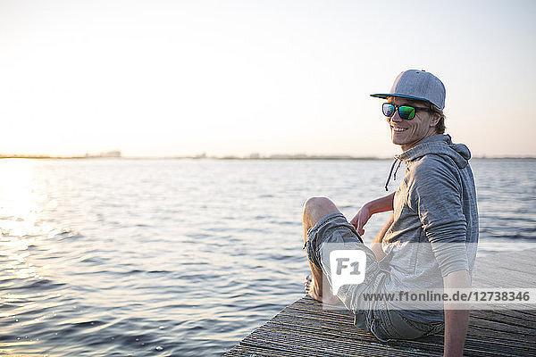 Smiling man sitting on wooden boardwalk at sunset