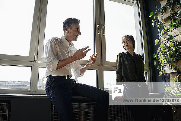 Businessman and businesswoman talking at the window