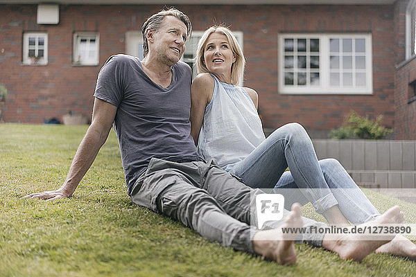 Smiling mature couple sitting in garden of their home