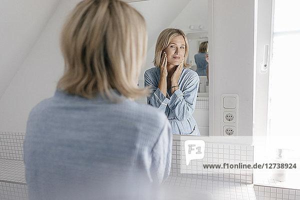Mature woman looking in bathroom mirror