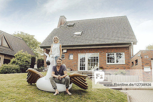 Portrait of smiling mature couple with inflatable pool toy in garden of their home