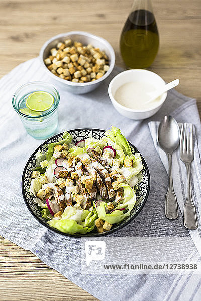 Bowl of Caesar salad with meat and red radish