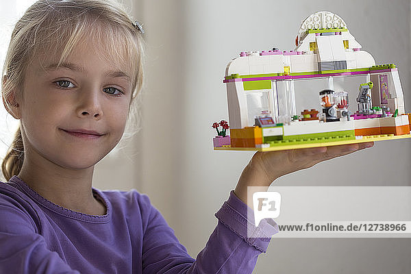 Portrait of smiling little girl presenting toy house