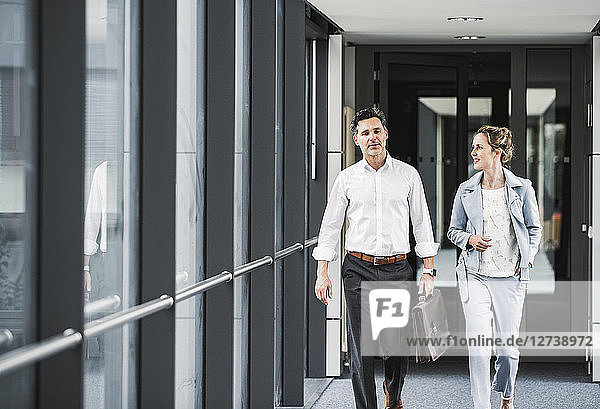 Businesswoman and businessman walking in office passageway