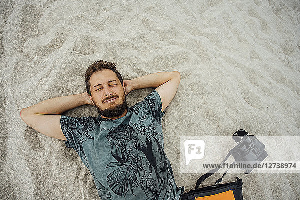 Man with binoculars resting on the beach
