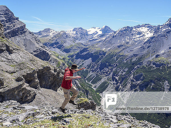 Italy  Lombardy  Sondrio  hiker jumping with view to Stelvio Pass and Ortler