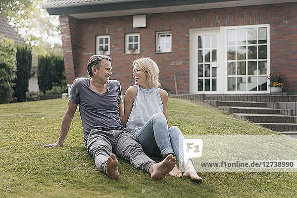 Happy mature couple sitting in garden of their home
