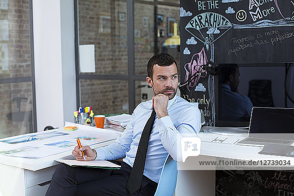 Businessman in creative office taking notes at desk