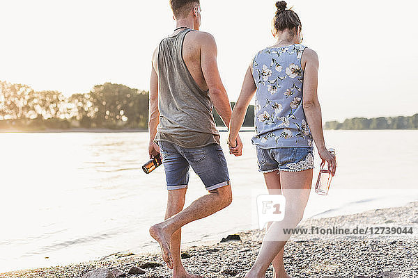 Young couple walking at the riverbank
