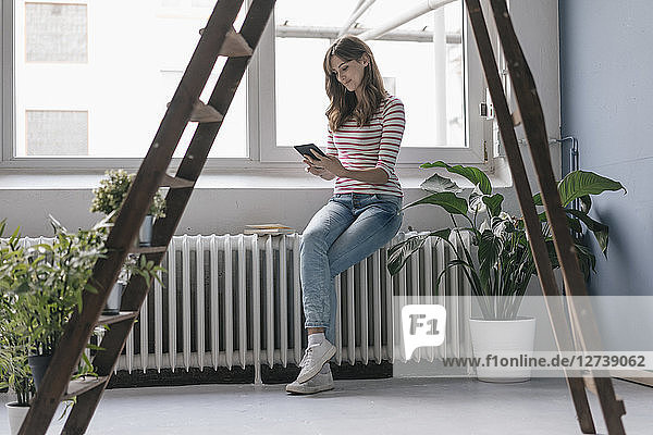 Woman sitting on radiator in her new home  reading e-book  surrounded by plants