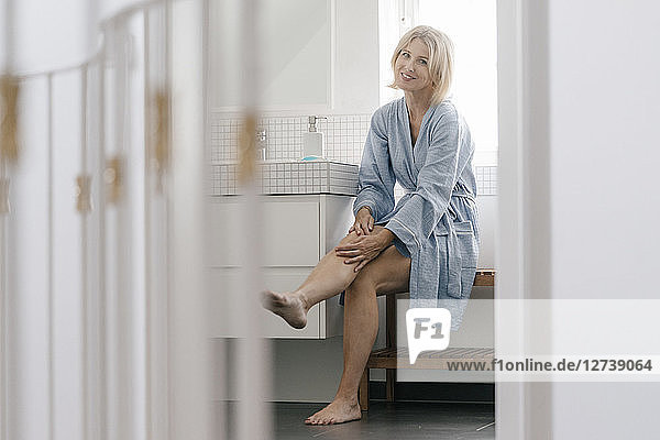 Portrait of smiling mature woman sitting in bathroom touching her legs