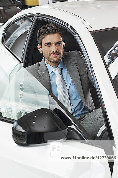 At the car dealer  Man sitting in new car