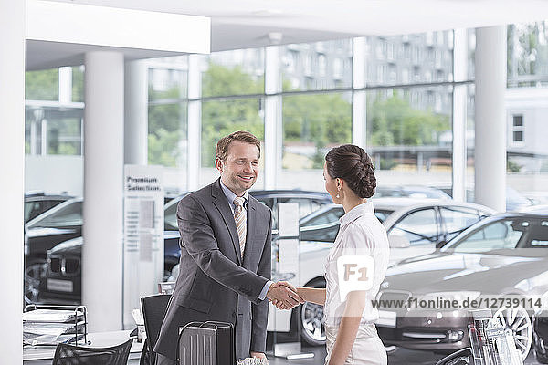 At the car dealer  Salesman and client shaking hands