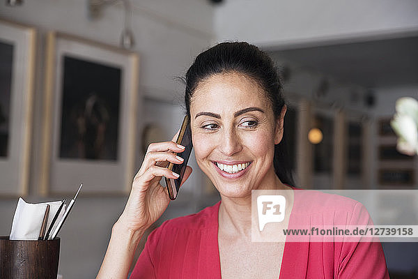 Mature woman sitting in cafe  talking on the phone
