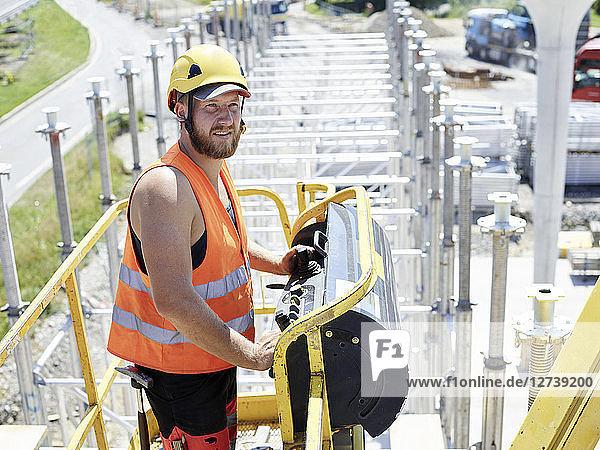 Worker on construction site navigating hoist