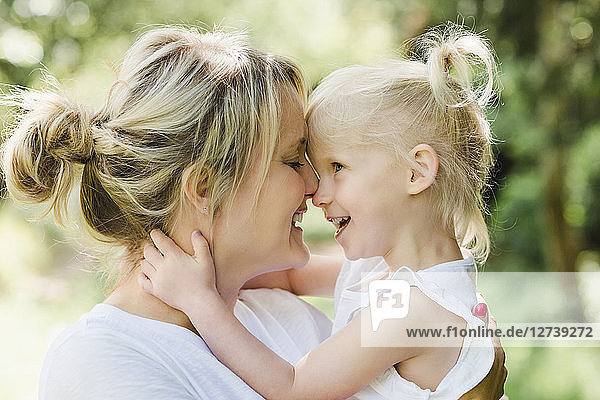 Happy mother cuddling her daughter in nature