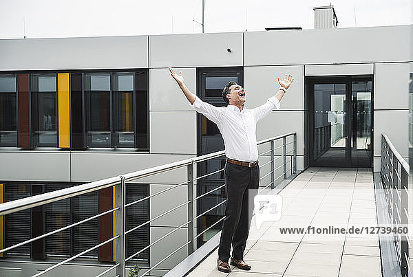 Cheering businessman standing on skywalk at office building