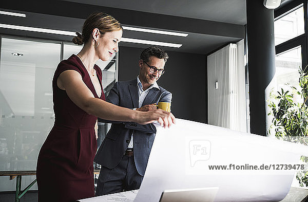 Businesswoman presenting plan to businessman in office at desk