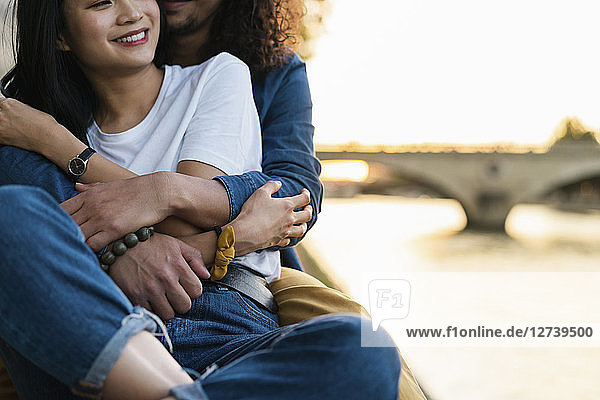 France,  Paris,  happy young couple hugging at river Seine at sunset