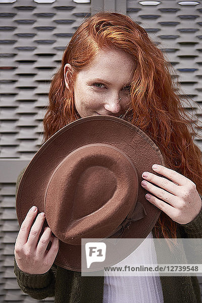 Portrait of smiling redheaded woman with brown hat