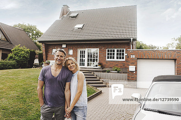 Portrait of smiling mature couple standing in front of their home