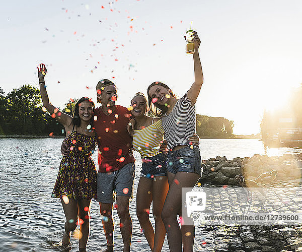 Confetti around group of happy friends having fun in a river at sunset