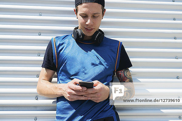 Tattooed young man with headphones looking at cell phone