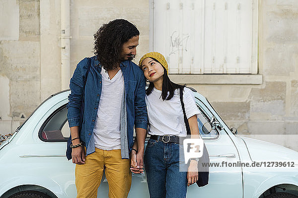 Young couple in love standing at small car