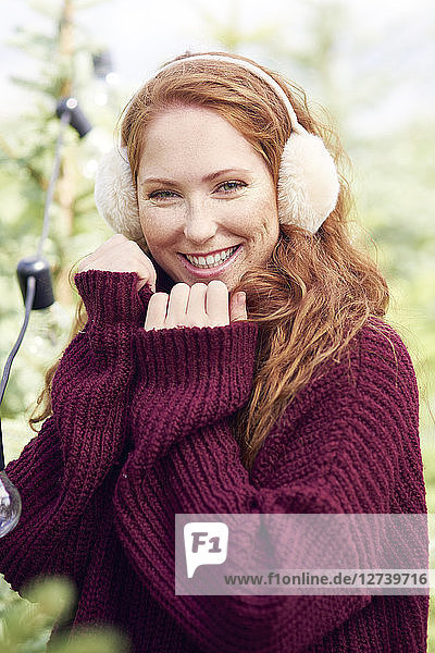 Portrait of happy redheaded young woman wearing ear muff and knit pullover