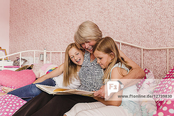 Grandmother sitting on bed with her granddaughters reading a book