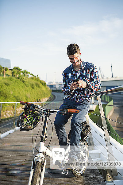 Smiling young man with bicycle looking at smartphone