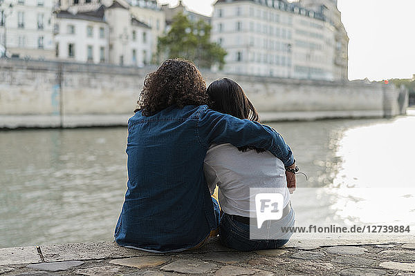 France  Paris  rear view of young couple sitting on a wall at river Seine
