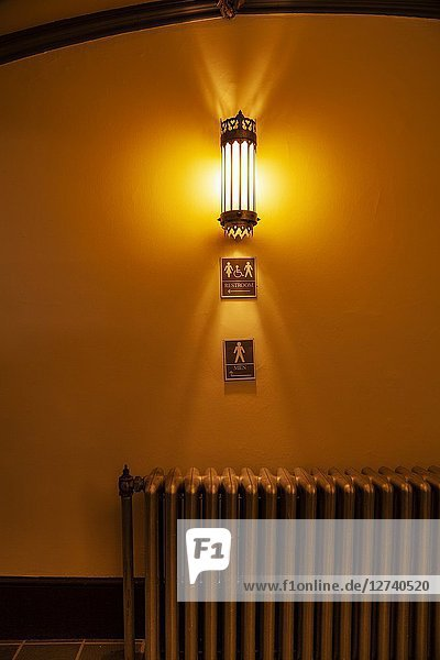 Light fixture on a wall with old cast iron radiator and signs reading ' Restroom' and 'Men' below it.