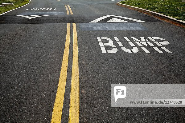 Street with double yellow lines  speed bumps  and the word 'Bump' painted on it.