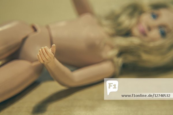Naked blonde female doll lying on its back.