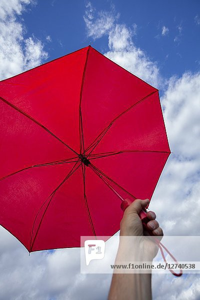 Man's hand holding a red umbrella against a cloudy sky.