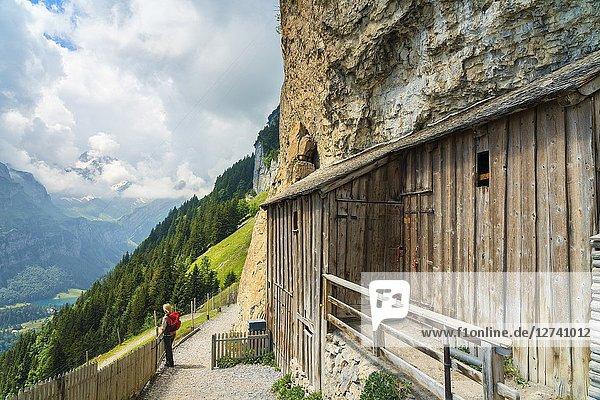 Woman looks at the green valley  Aescher-Wildkirchli Gasthaus  Ebenalp  Appenzell Innerrhoden  Switzerland.