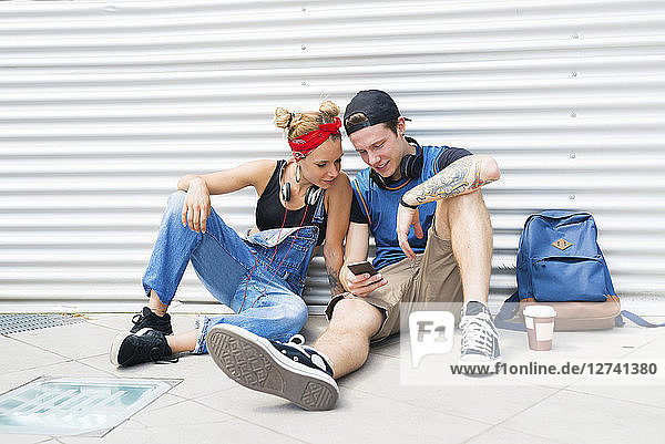 Young couple sitting on ground looking at smartphone