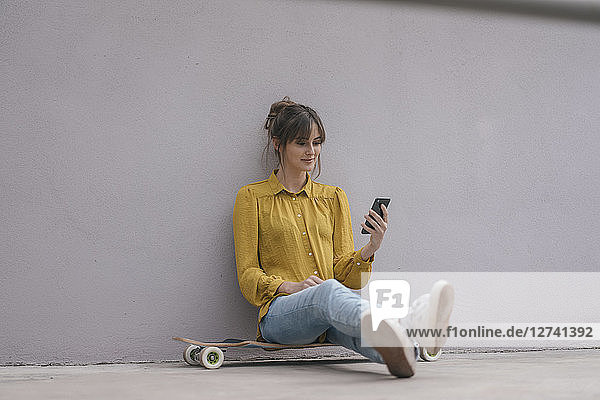 Young woman sitting on skateboard  using smartphone
