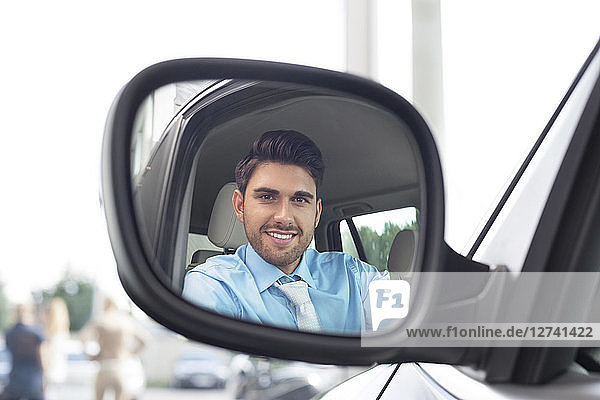 At the car dealer  Reflection of man in wing mirror