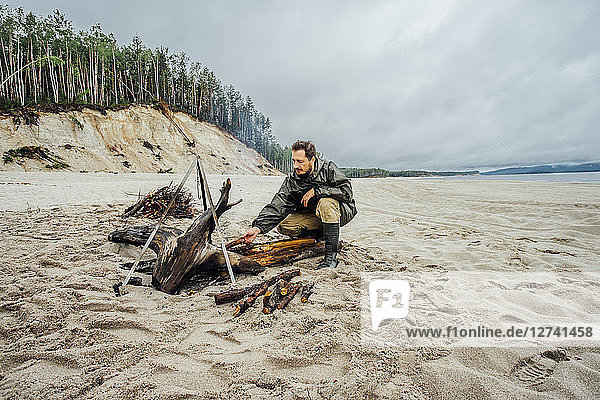 Man collecting firewood on the beach  preparing campfire