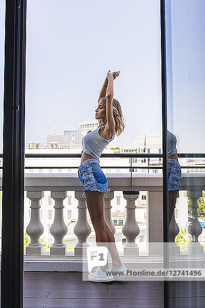 Blond woman standing on balcony  stretching